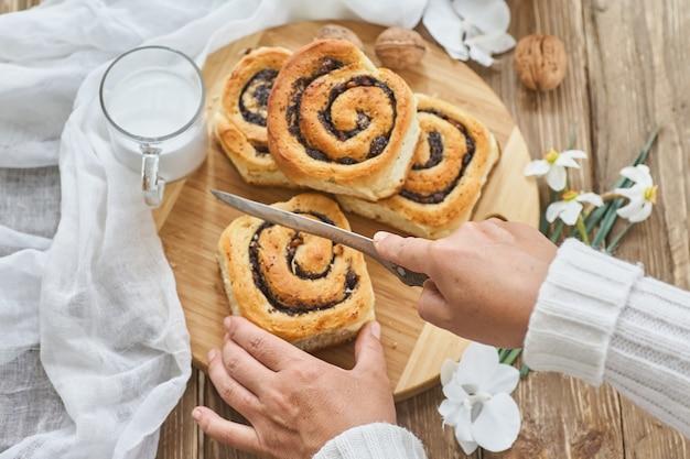 女性の手カットの自家製パン、ジャム、古い木製のテーブルにクルミと牛乳のカップを提供しています