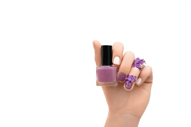 白い背景に分離された紫色のマニキュアボトルを保持しているライラック色の花で飾られた女性の手。春のコンセプトです。