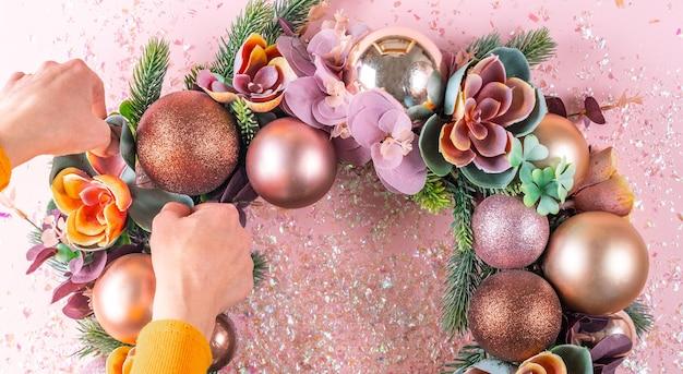 Женская рука украшает красивый необычный рождественский венок