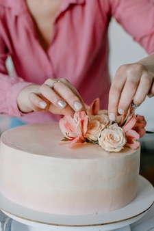Female hand decorating pink flower wedding birthday cake on stand.