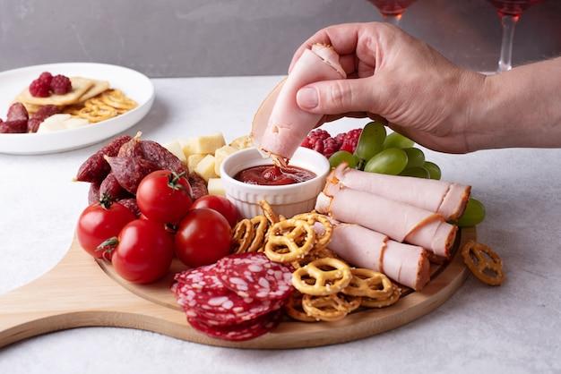 ソーセージ、チーズ、クラッカー、フルーツ、前菜のプレート、クローズアップを添えた丸い豚肉のボードにハムのスライスをソースに浸した女性の手。