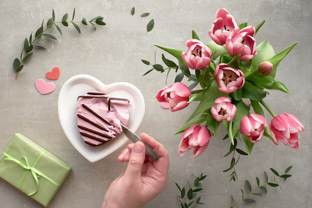 Female hand dipping a spoon in pink heart ice cream and pink tulips