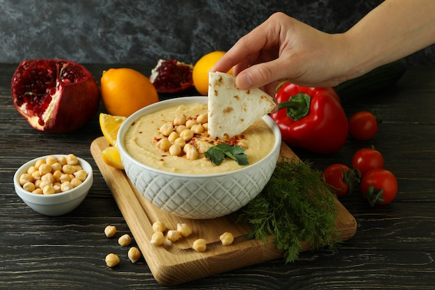 Female hand dips pita in tasty hummus on wooden table