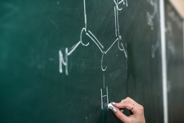 Female hand draws chemical equations on a blackboard. lesson in school