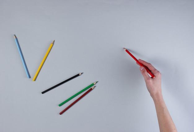 Женская рука рисует цветной карандаш на серой поверхности.