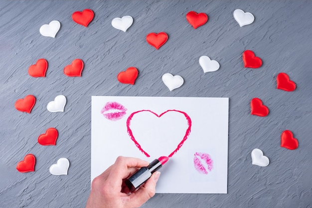 Female hand draws a heart shape lipstick on white paper with lipstick kisses on a gray wooden background