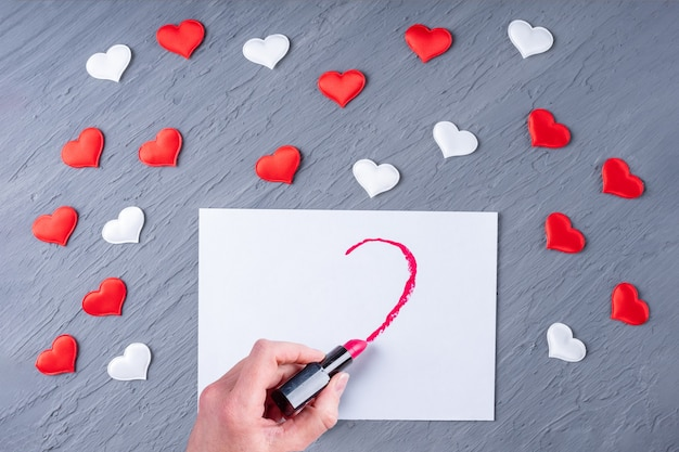 Female hand draws with lipstick half a heart shape on white paper on a gray wooden background