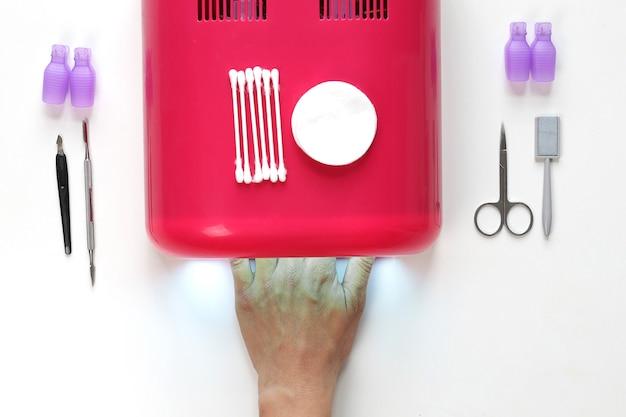 女性の手は白い背景の上の赤いuvランプの上面図のクローズアップで爪を乾かします