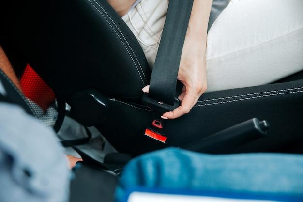 女性の手がシートベルトを締めます。黒のシートベルトを保持している白いジーンズの女性のクローズアップカットビュー。交通安全の概念。意識的な運転コンセプト。