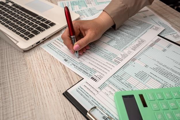 사무실에서 도움말 계산기와 노트북으로 미국 세금 양식 1040을 채우는 여성 손