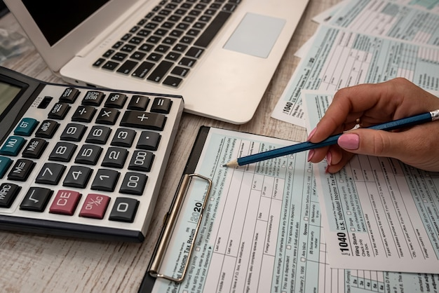 Female hand  filling us tax form 1040 with help calculator and laptop in the office