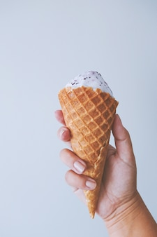 Female hand fingers hold a waffle cone with ice cream