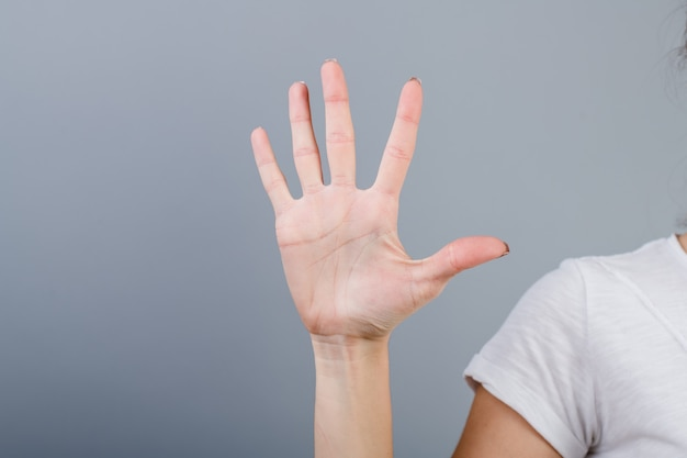 Female hand in fist showing five fingers isolated over grey