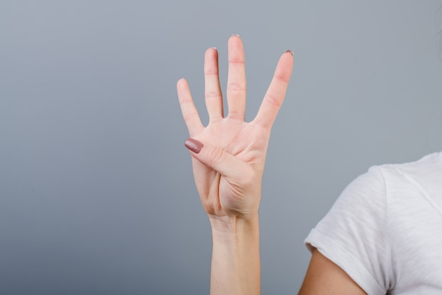 Female hand in fist showing four fingers isolated over grey