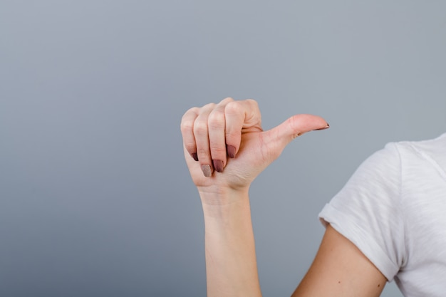 Female hand in fist showing one finger isolated over grey