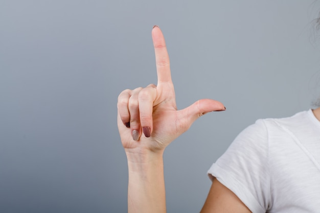 Female hand in fist showing two fingers isolated over grey
