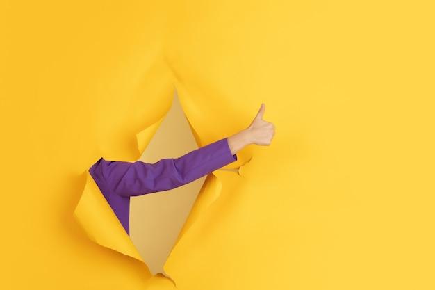 引き裂かれた黄色の紙の穴の背景で身振りで示す女性の手