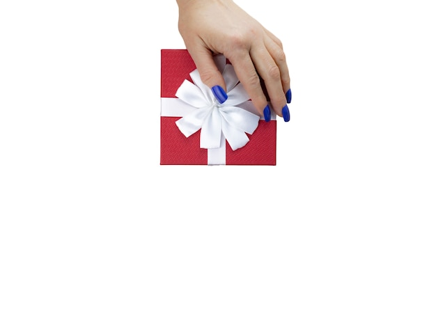Female hand on gift box red color with white ribbon isolated on white table. close up. selective soft focus. top view. text copy space.