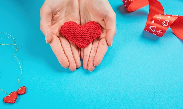 Female hand give a knitted heart