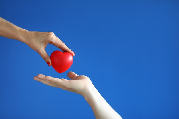 Female hand give red heart to male hand on blue space close-up.