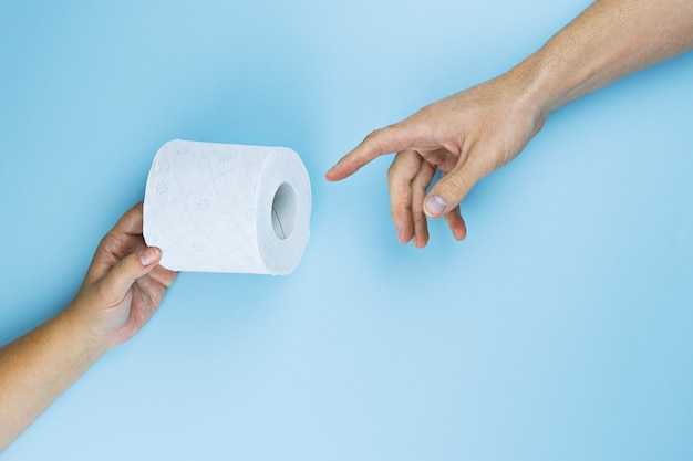 Female hand gives toilet paper roll to male hand on blue background