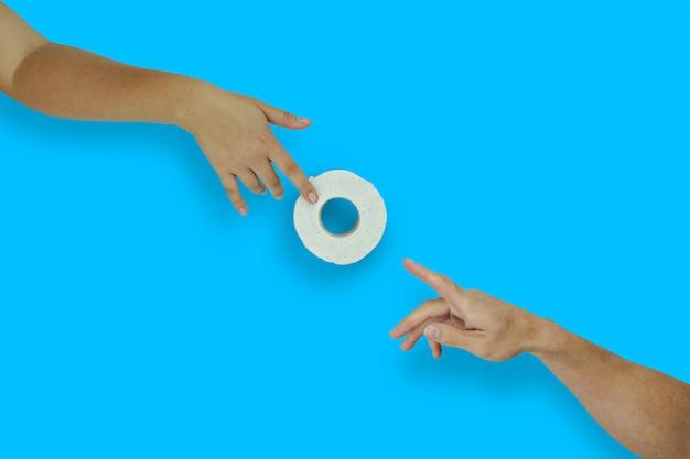 女性の手が青色の背景に男性の手にトイレットペーパーのロールを与える