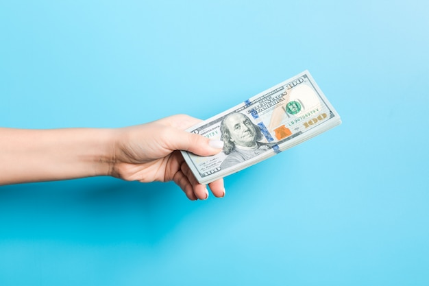 Female hand giving a bundle of dollar bills on blue . power and wealth