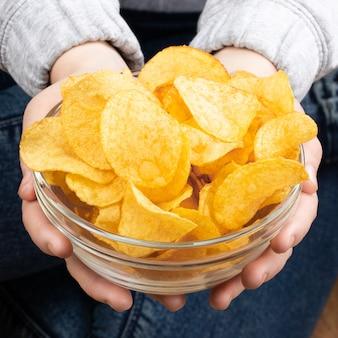 바삭한 감자 칩 그릇을주는 여성 손