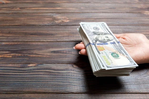 Female hand giving one hundred dollar bills on wooden background