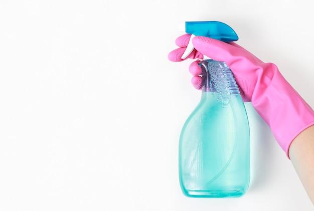 Female hand in glove holds window spray