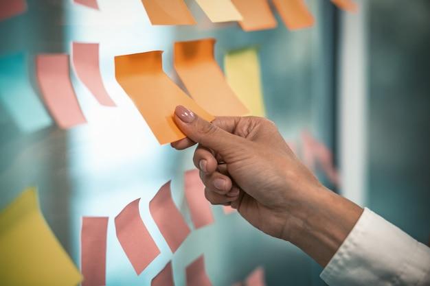 女性の手は、オフィスの窓に空のステッカーを接着します。ガラスの壁に貼り付けられたテキスト用のスペースを持つ多くのカラフルなメモ用紙ステッカー。着色画像。