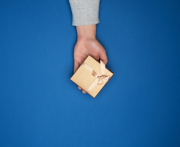 Female hand in a gray sweater holds a closed square cardboard gift box with a bow