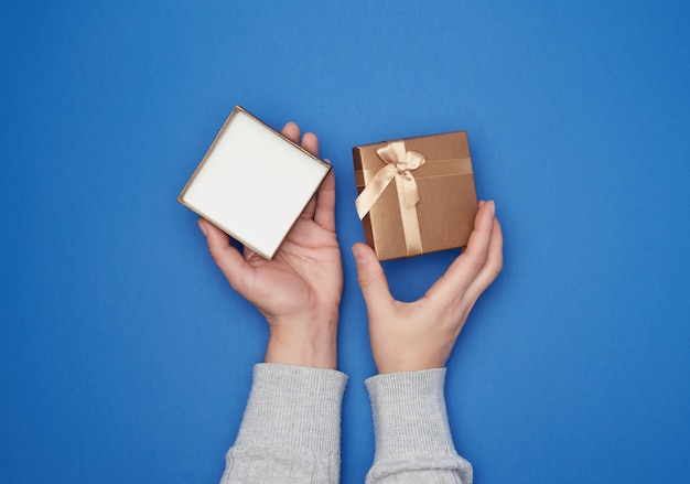 Female hand in a gray sweater holds open square cardboard gift box
