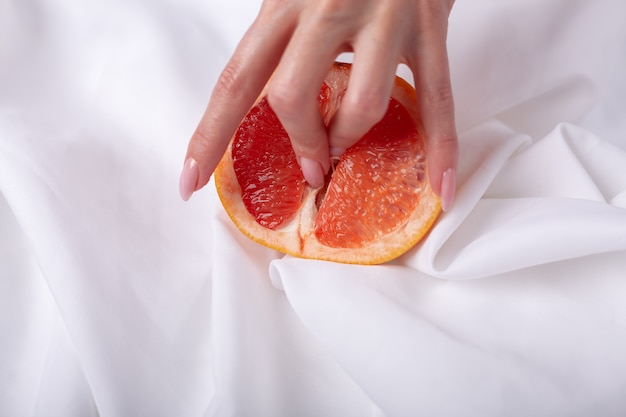 Female hand and half of juicy grapefruit. erotic concept