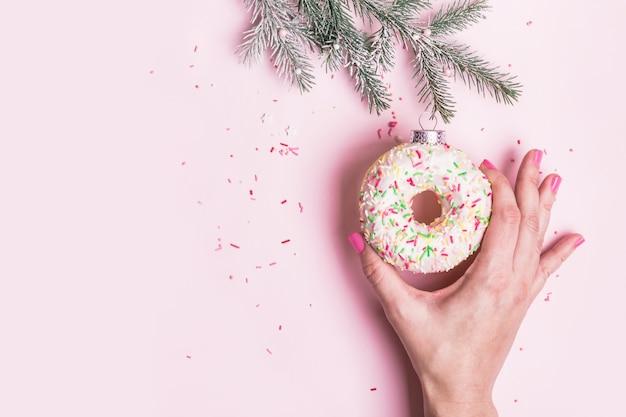 여성의 손은 분홍색 배경에 도넛으로 만든 크리스마스 값싼 물건 장식을 걸고 있습니다. 크리스마스 크리에이 티브 개념입니다.