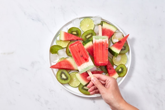 In the female hand, a healthy berry icy popsicle against the background of a gray marble table with a plate with slices of watermelon, kiwi, lime and ice cubes. space for text. flat lay