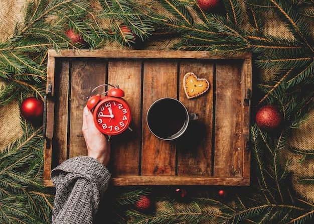 女性の手は、トレイのお茶とクリスマスツリーの横に目覚まし時計を保持します
