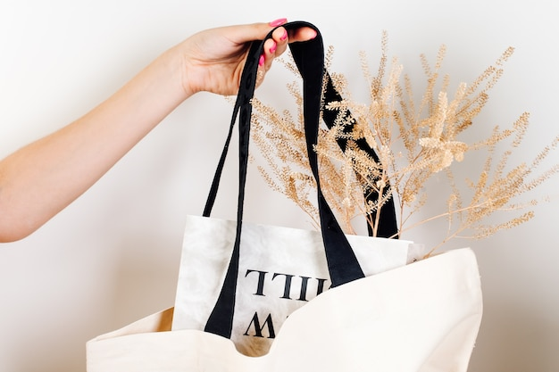 Female hand hold bag mockup of reusable white cotton ecobag with black handles with dry flowers and ...