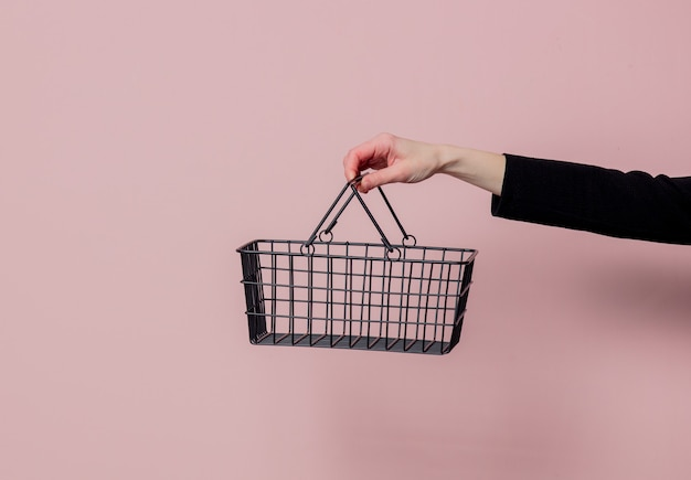 Female hand hold black metal supermarket busket on pink wall