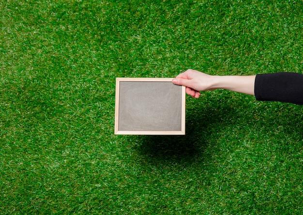 Женская рука держит доску над зеленой травой