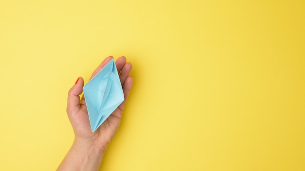 Female hand hold a blue paper boat on a yellow background. mentoring and support concept, top view
