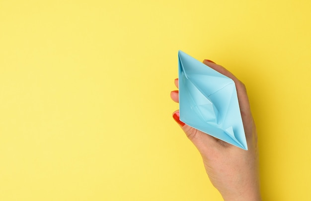 Female hand hold a blue paper boat on a yellow background