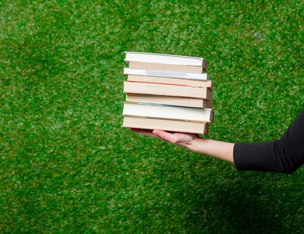 Female hand hold books over green grass