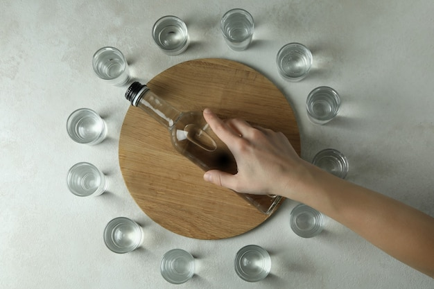 Female hand hold bottle of drink on wooden tray on white textured wall with shots