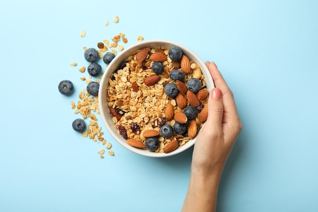 Female hand hold bowl with granola on blue background