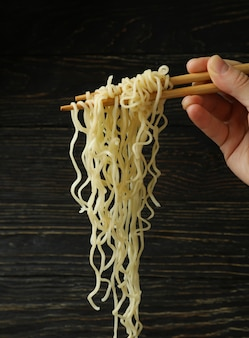 Female hand hold chopsticks with noodles on wooden