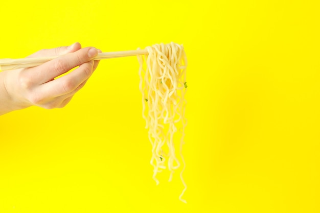 Female hand hold chopsticks with noodles on yellow