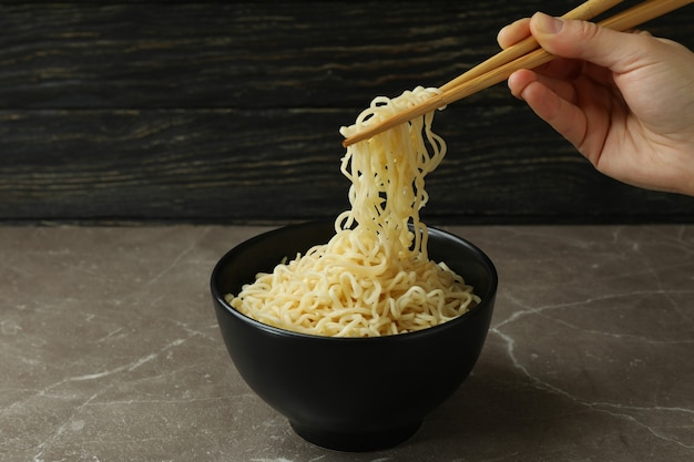 Female hand hold chopsticks with noodles