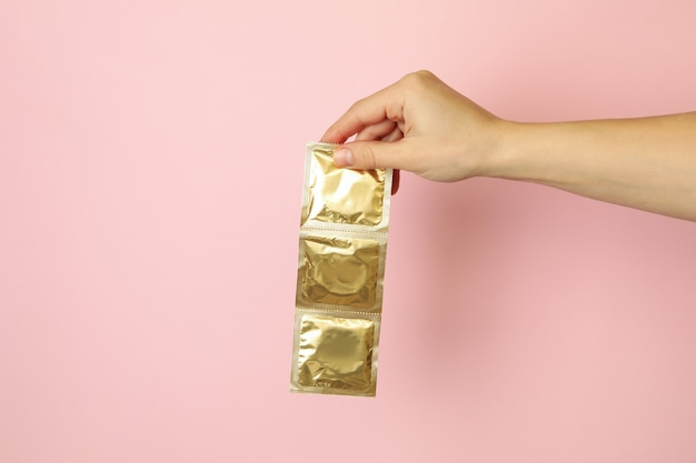 Female hand hold condoms on pink background, space for text