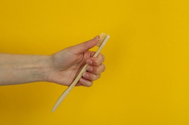 女性の手は黄色の背景に環境に優しい歯ブラシを保持します